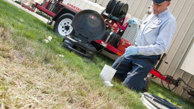 Plombier évacue une canalisation avec un camion de pompage