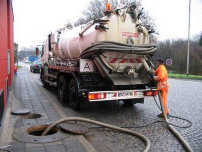 Plombier évacue l'eau de canalisation avec un camion de pompage