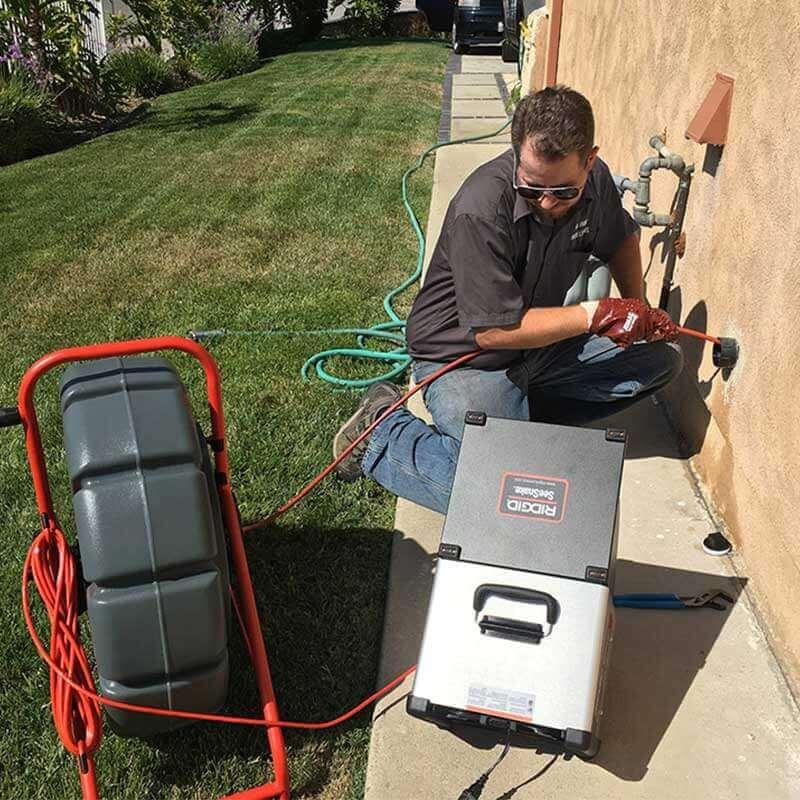 plombier qui inspecte une canalisation avec une caméra vidéo
