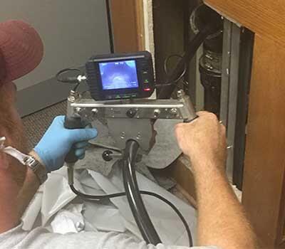 plombier qui recherche l'origine d'une fuite d'eau avec une caméra d'inspection